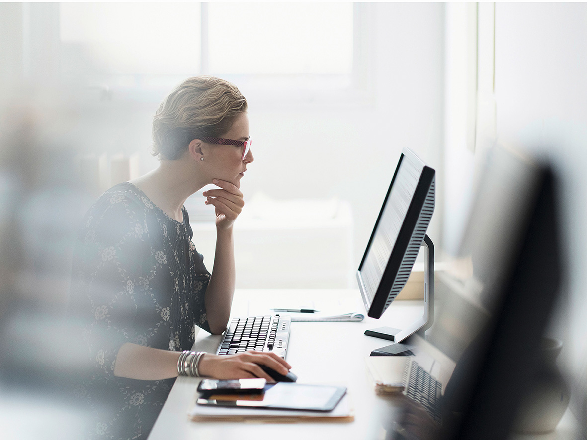 USA, New Jersey, Side view of business woman working on desktop pc in office